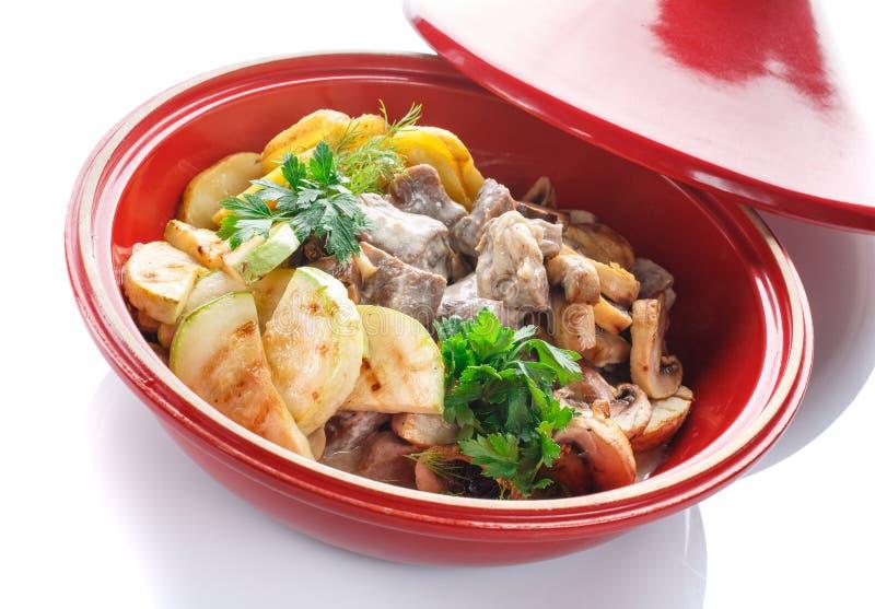 Stufato di verdure con carne, il fungo e le erbe su un fondo bianco fotografia stock