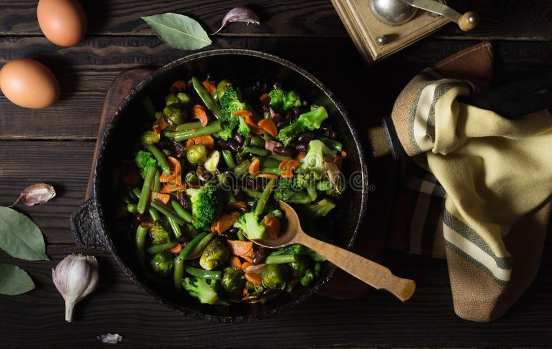 Stufato di verdure in una padella su una tavola di legno scura fotografia stock