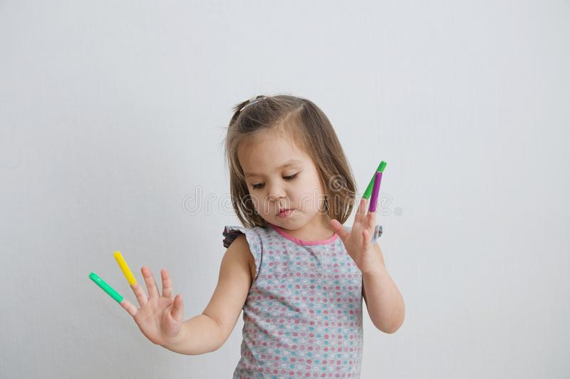 Stuff dancer.little girl playing with felt tip pens. baby girl painting and playing. colorful stuff felt pen caps on fingers. Little girl playing with felt tip stock images