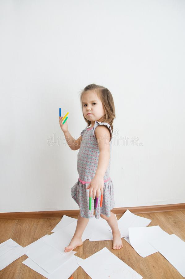 Stuff warrior. child playing with felt tip pens. baby girl painting and playing with stuff. colorful felt pen caps on fingers. Child playing with felt tip pens stock photo