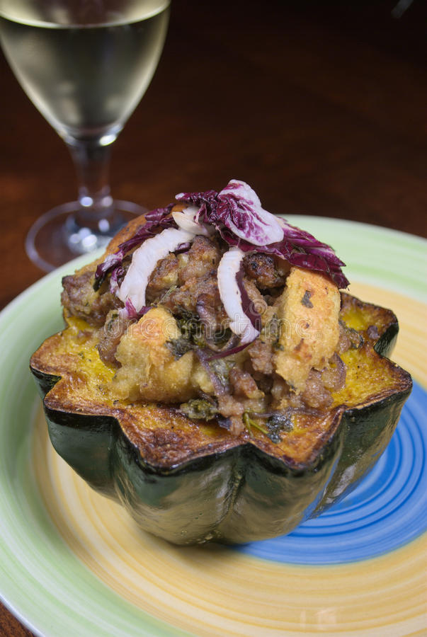 Stuffed Acorn Squash. Halved acorn squash stuffed with pork sausage, bread crumbs and topped with radicchio stock photography