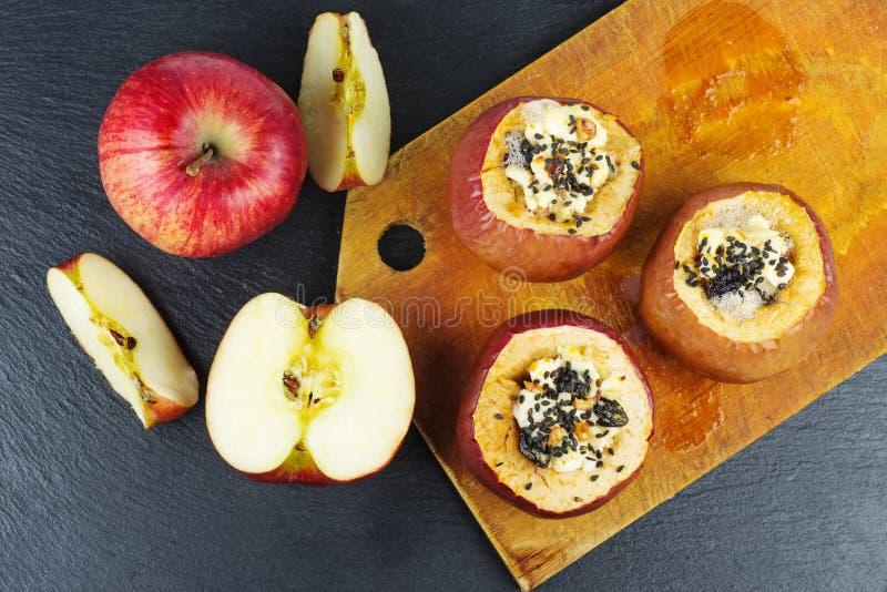Stuffed bakade äpplen med sezamefrö och valnötter över svarten kritiserar stenbakgrund royaltyfria bilder