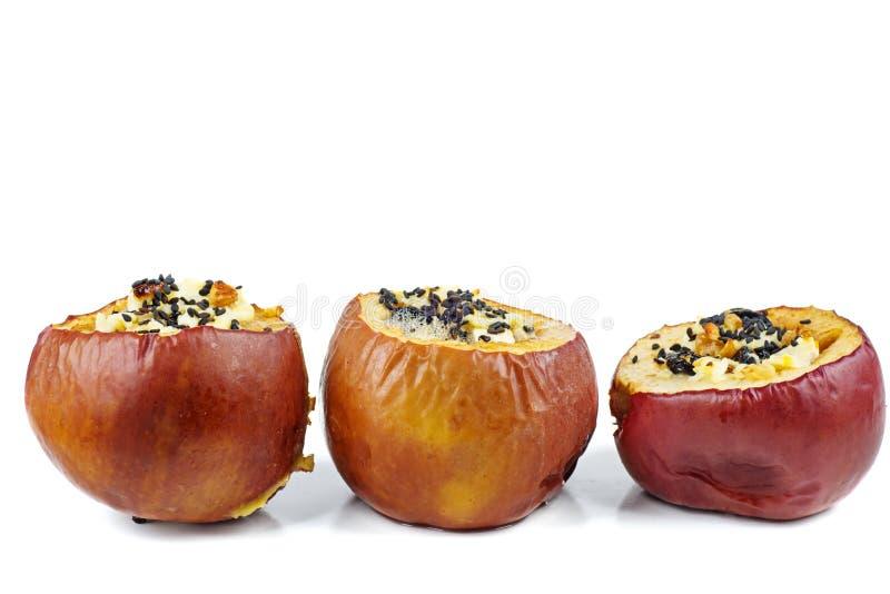 Stuffed bakade äpplen med sezamefrö och valnötter som isoleras på en vit bakgrund royaltyfri bild