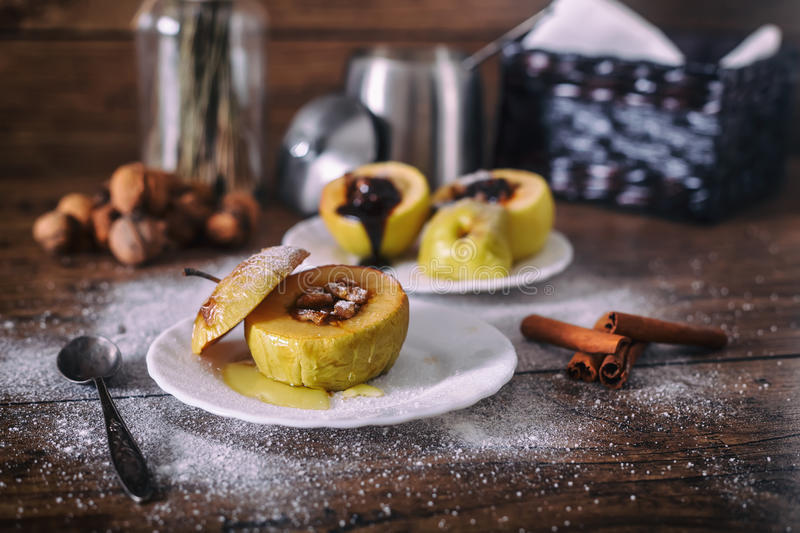 Stuffed baked apple with nuts, honey and chocolate on white dessert plates, dark wooden background. Christmas sweet. Stuffed baked apple with nuts, honey and stock photo
