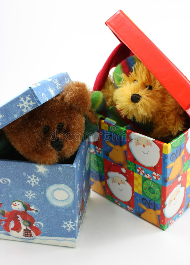 Stuffed bear toys peaking out of Christmas boxes royalty free stock images