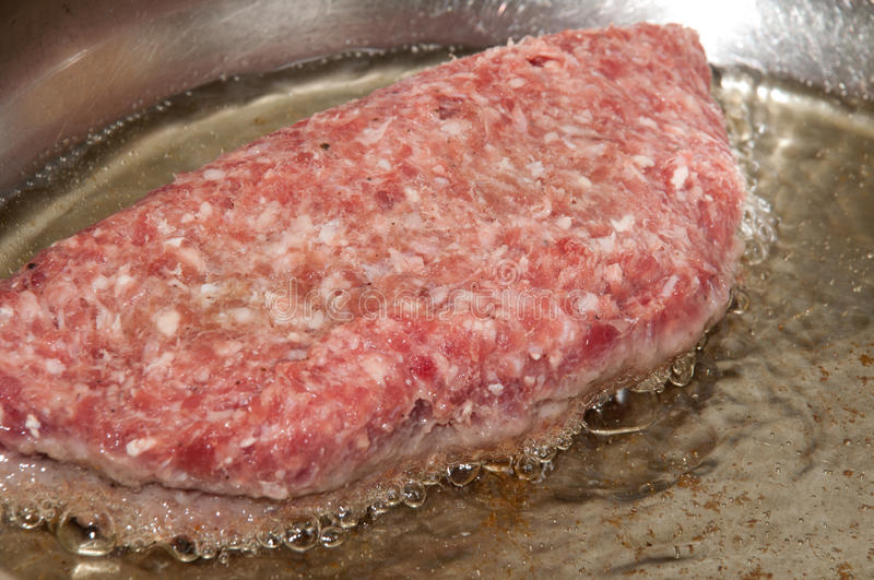 Stuffed burger in hot oil in a frying pan stock photo