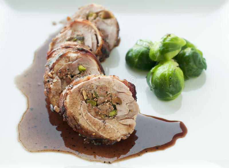 Stuffed Chicken. Stuffed bacon wrapped chicken thigh with wine sauce and brussel sprouts royalty free stock image