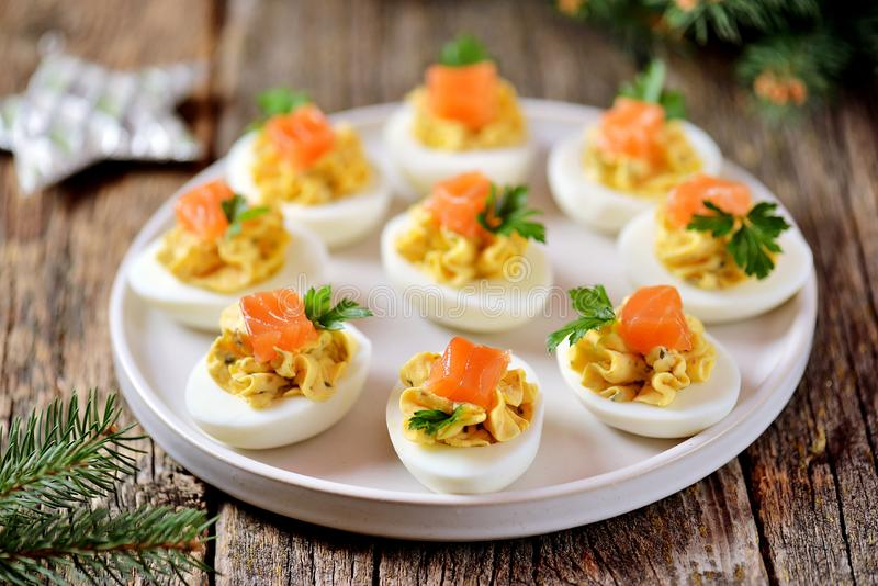 Stuffed chicken eggs with soft cheese, capers and salted salmon. Christmas background. stock photography