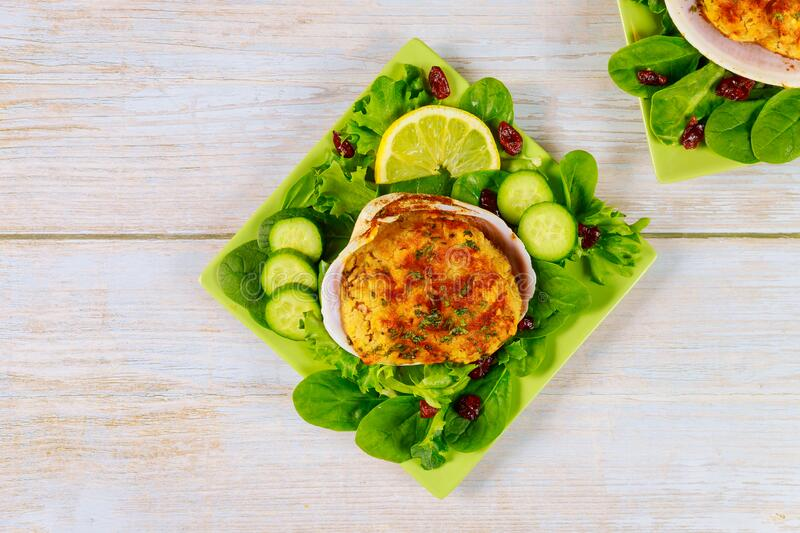Stuffed clam with crabmeat and bread crumbs with salad and lemon. Seafood concept royalty free stock image