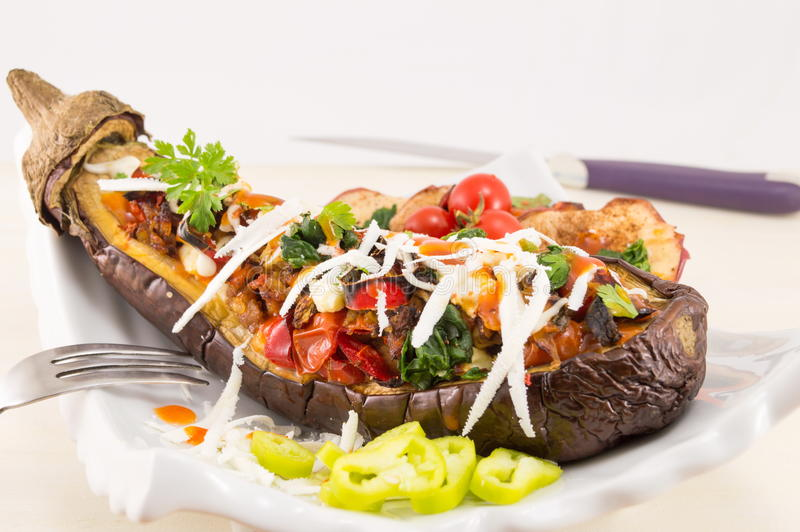 Stuffed eggplant on a plate. With cherry tomatoes and cottage cheese royalty free stock photo