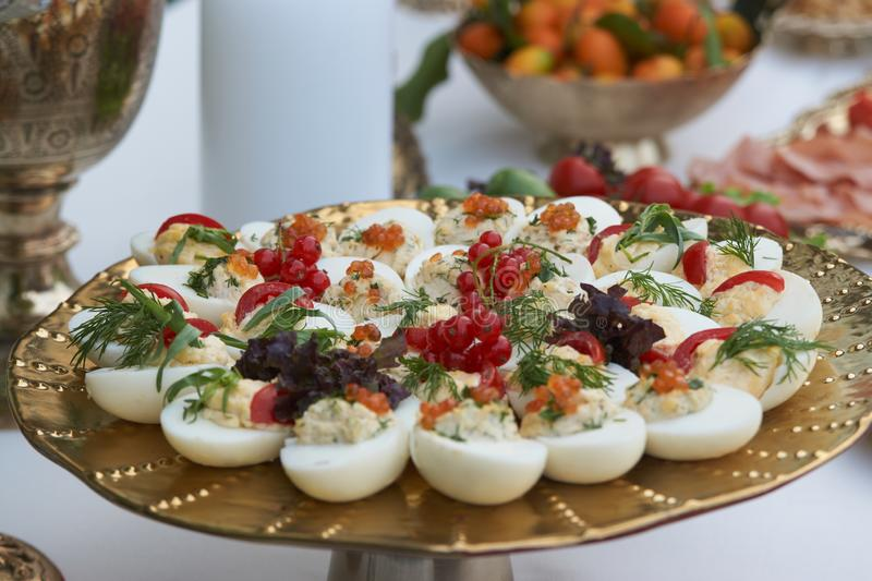 Stuffed eggs canapes with soft cheese chive and caviar. Healthy food. Catering service buffet food at wedding event table, close-up royalty free stock image