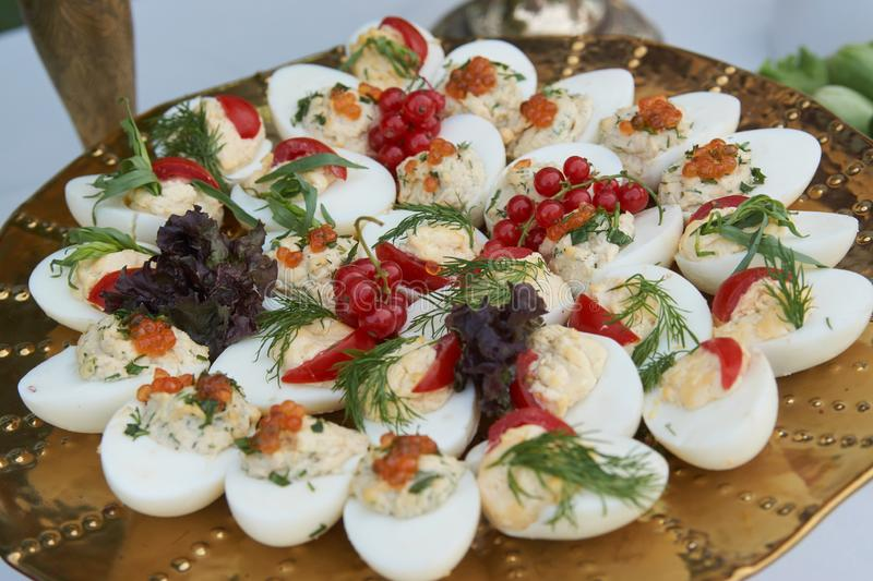 Stuffed eggs canapes with soft cheese chive and caviar. Healthy food. Catering service buffet food at wedding event table, close-up royalty free stock photos