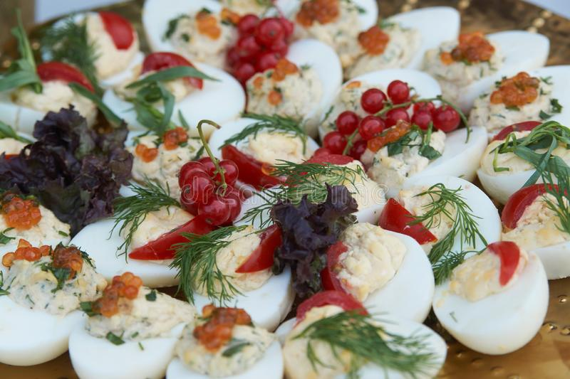 Stuffed eggs canapes with soft cheese chive and caviar. Healthy food. Catering service buffet food at wedding event table, close-up stock photography