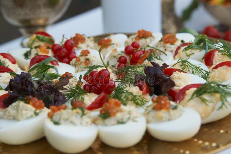 Stuffed eggs canapes with soft cheese chive and caviar. Healthy food. Catering service buffet food at wedding event table, close-up stock images