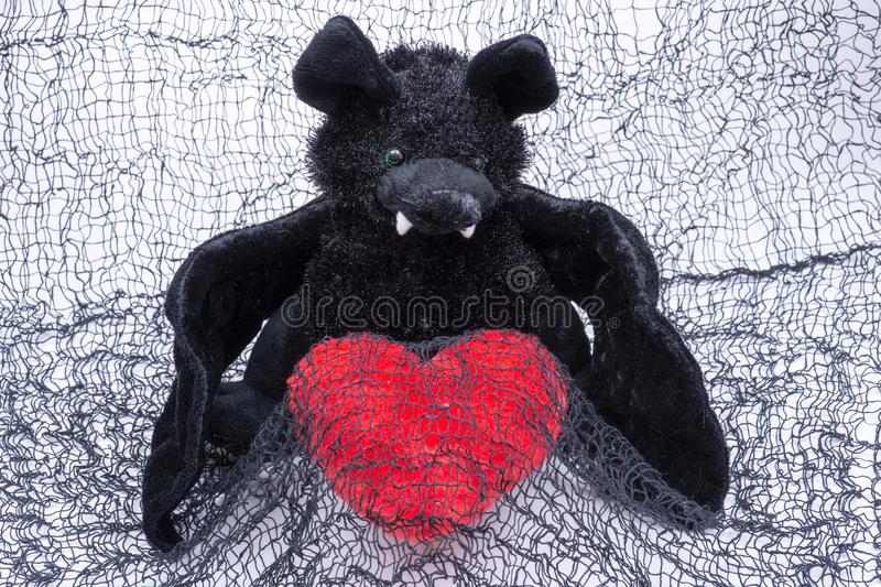 Stuffed funny black bat toy with red fluffy heart on creepy cotton web cloth. Stuffed funny black bat toy with red fluffy heart on creepy black cotton web cloth stock image