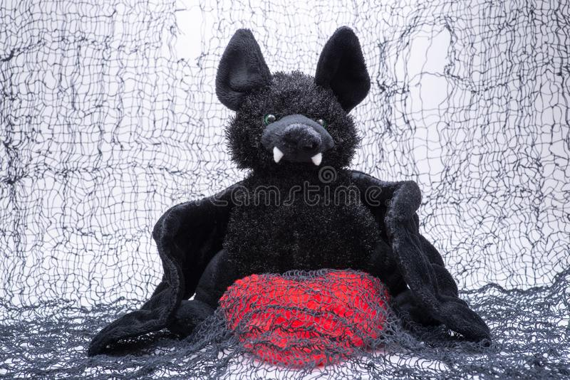 Stuffed funny black bat toy with red fluffy heart on creepy cotton web cloth. Stuffed funny black bat toy with red fluffy heart on creepy black cotton web cloth stock photo