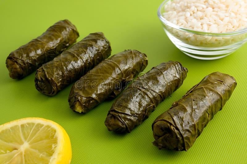 Stuffed grape leaves. Delicious stuffed grape leaves the traditional dolma of the mediterranean cuisine on green cutting board with lemon slice and small glass royalty free stock images