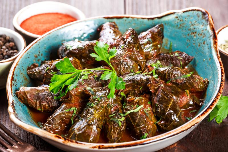 Stuffed grape leaves with rice and herbs on plate on wooden background - Dolma, tolma, sarma. stock photos