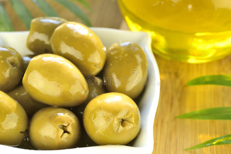 Stuffed green olives and olive oil macro stock photo
