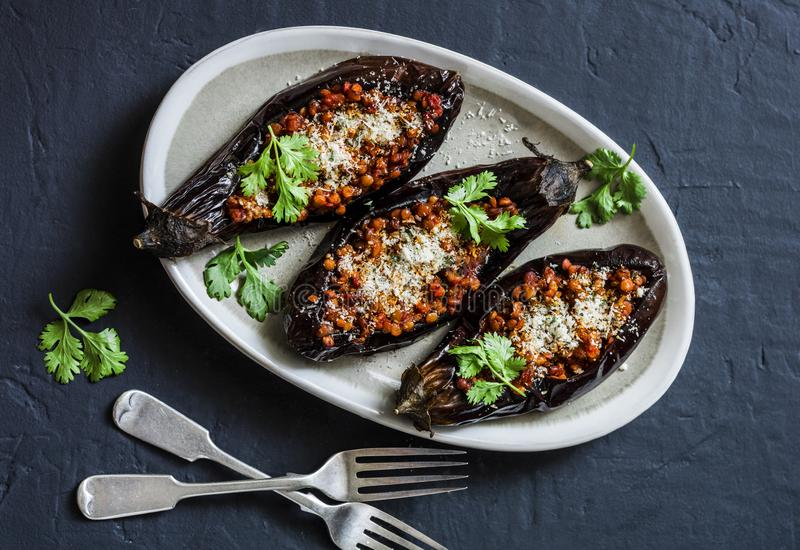 Stuffed lentils roasted eggplant - delicious healthy vegetarian lunch, snack, appetizer on a dark background stock images