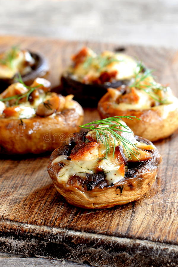 Stuffed mushrooms with cheese and fried meat. Baked mushroom caps with filling. Appetizer on a wooden board photo. Closeup. Stuffed mushrooms appetizer recipe royalty free stock image