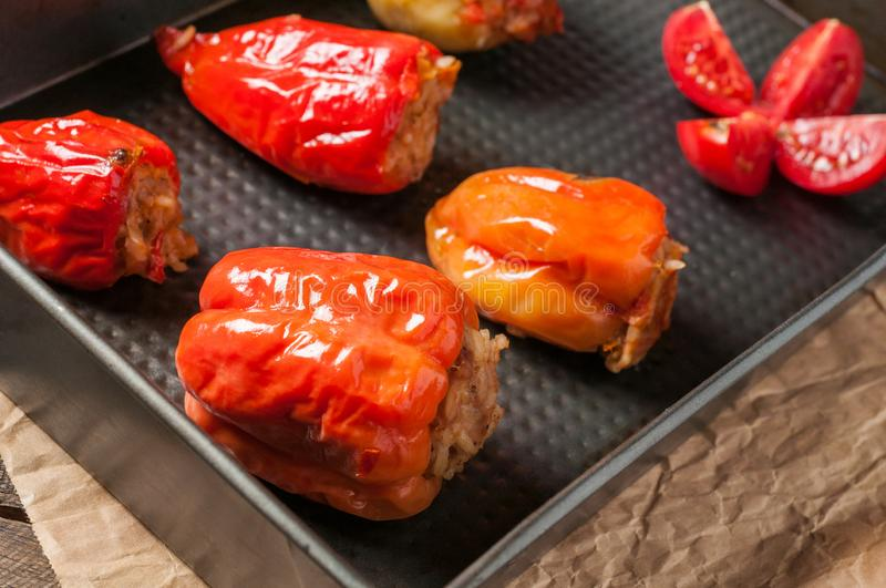 Stuffed pepper and tomato in rectangular metal tray lies on crumpled paper and old brown wooden table. Stuffed pepper and tomato in rectangular metal tray lies royalty free stock photography