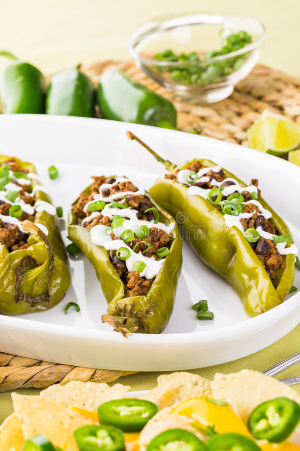 Stuffed peppers. Chipotle beef & bean stuffed chile peppers garnished with sour cream and scallions stock photos