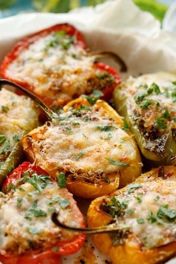 Stuffed peppers,  halves of peppers stuffed with bulgur, dried tomatoes, herbs and cheese in a baking dish ,close-up, royalty free stock photography