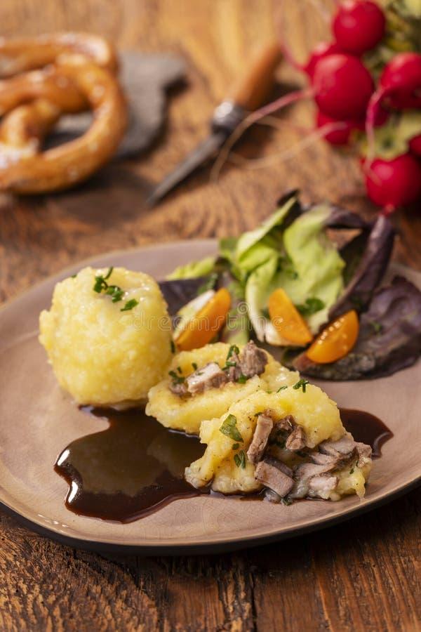Stuffed potato dumplings. With salad on wood stock photo