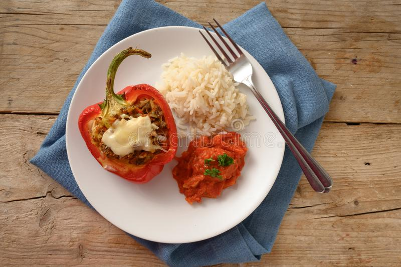Stuffed red bell pepper baked with cheese gratin, rice and tomato sauce on a plate and a blue napkin, rustic wooden table, copy stock images