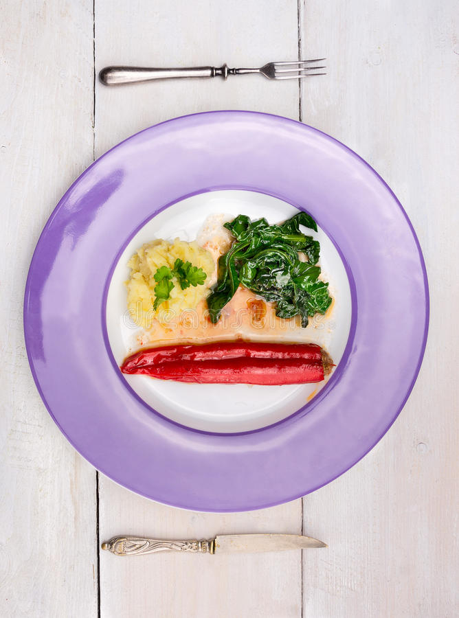 Stuffed Red peppers with mashed potatoes and spinach in purple plate stock photo
