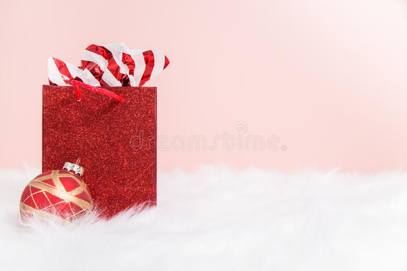 A stuffed red sparkly gift bag on white fur. With a pink background stock photos