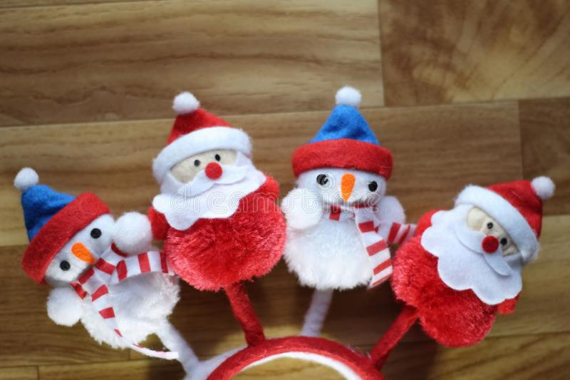 stuffed Santa claus and snowmen side by side on brown wood background royalty free stock photos