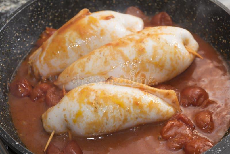 Stuffed squids with tomato sauce. Stuffed squids stir-fried with tomato sauce stock photos