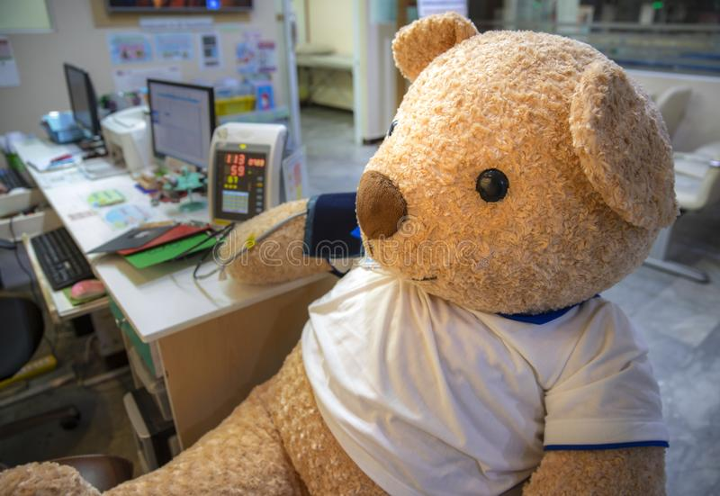 A stuffed toy bear in the clinic screening area. A cute live size stuffed toy bear sitting the clinic screening area having blood pressure measured. A campaign royalty free stock photos