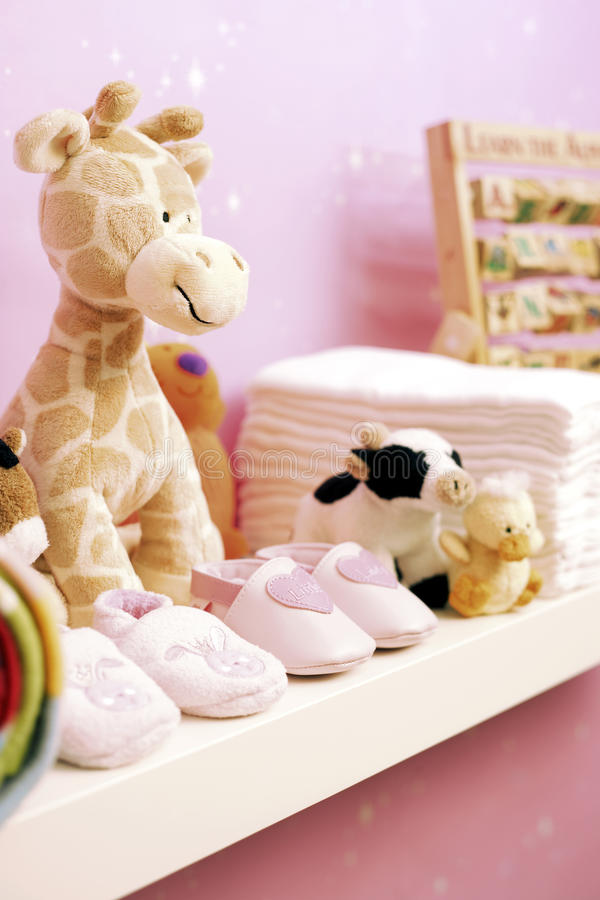 Stuffed toys shoes and nappies on shelf in baby's room stock images