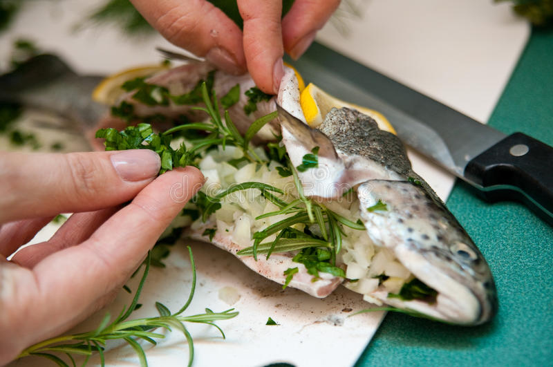 Stuffed trout with lemon dish. Delicious dish of trout fish stuffed with onion, basil and herbs, decorated with lemon stock photos