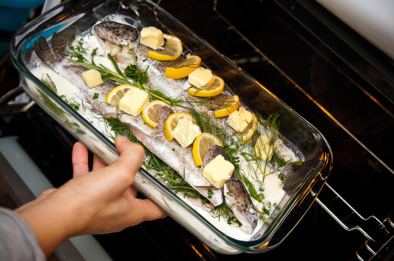 Stuffed trout with lemon dish. Delicious dish of trout fish stuffed with onion, basil and herbs, decorated with lemon stock images