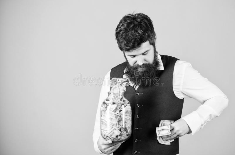 Stuffing some cash into his pockets. Bearded man hiding away cash holdings. Businessman taking cash money out of glass. Jar. Cash flow budget, copy space stock image