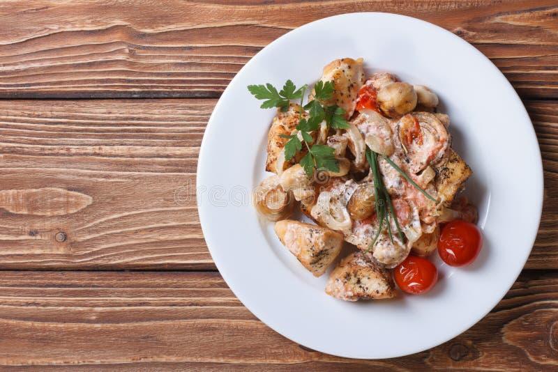 Stufi il pollo con i funghi su una vista superiore del piatto bianco immagini stock