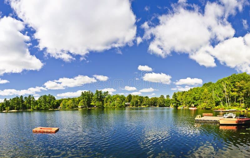 Stuga lake med den dykningplattformen och docken fotografering för bildbyråer