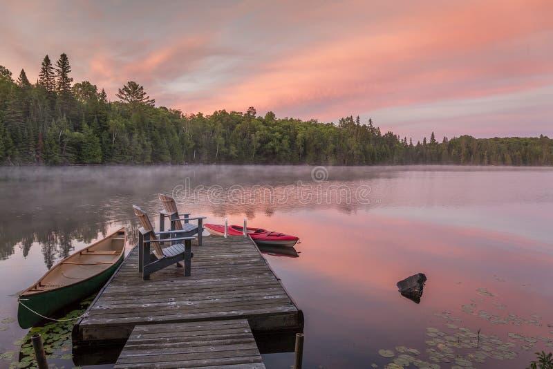 Stugaskeppsdocka på en kanadensisk sjö på gryning på gryning arkivfoto
