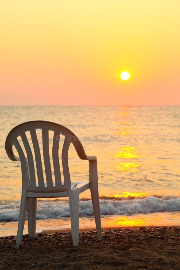 Stuhl ist auf Küste. schöner orange Sonnenuntergang stockfotografie