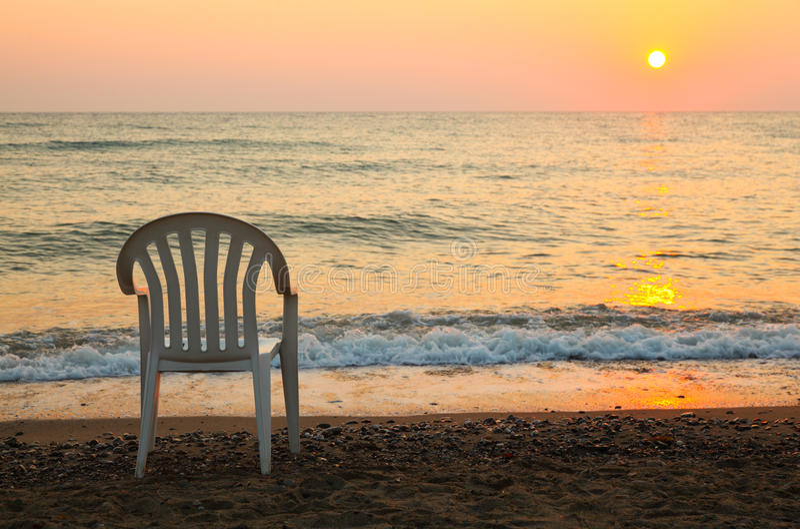 Stuhl ist auf Küste. schöner orange Sonnenuntergang lizenzfreies stockbild