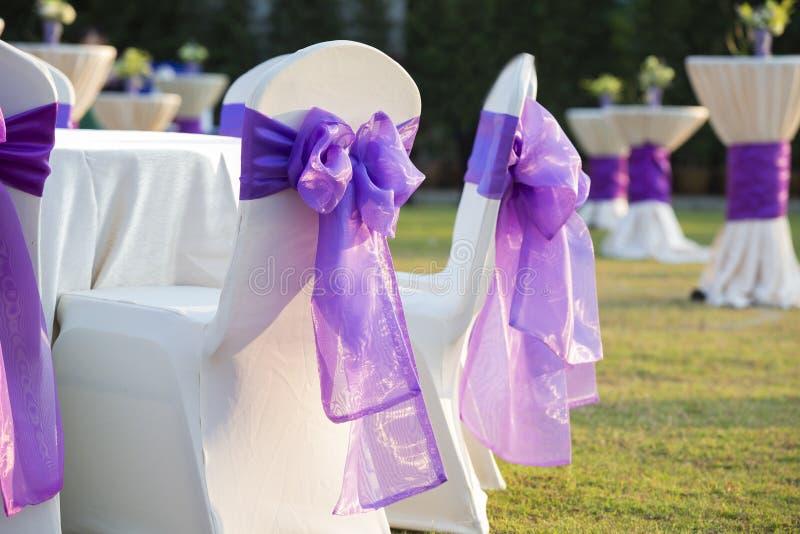 Stuhl mit einem purpurroten Bogen in einer schönen Hochzeit stockbild