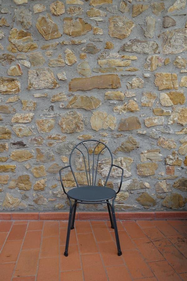 Stuhl mit mittelalterlicher Wand im Hintergrund Hotel oder Café in Toskana, stockfoto