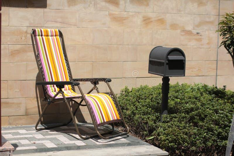 Stuhl nahe Postbox lizenzfreie stockfotos