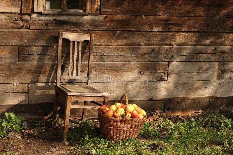 Stuhl und Basketful der Äpfel stockbilder