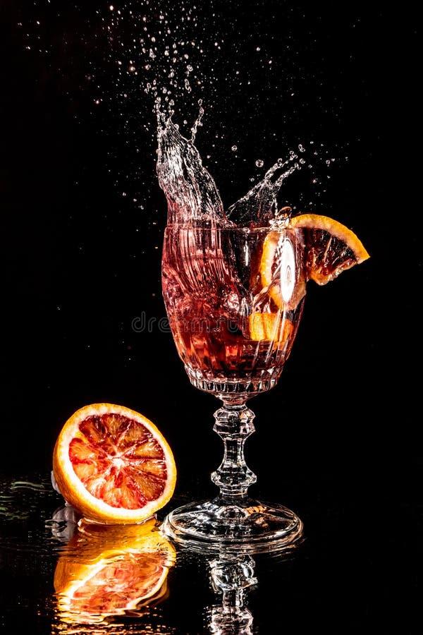 Stuk die van sinaasappel in een glas champagne vallen stock foto