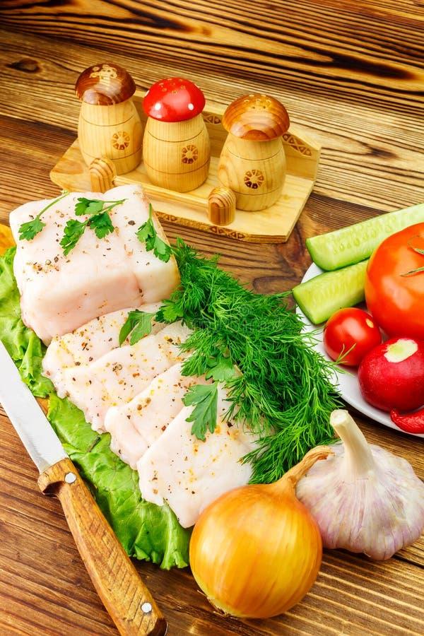 Stuk en gesneden verse varkensvleesreuzel, vers product, greens, groenten op de houten raad en mes op lijst royalty-vrije stock foto's
